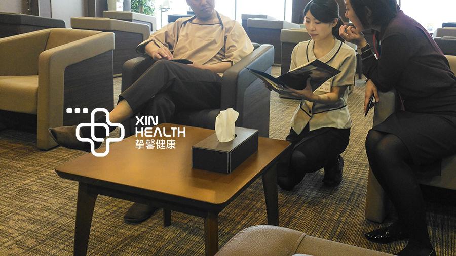 日本高级体检护士蹲在地上为用户介绍体检流程