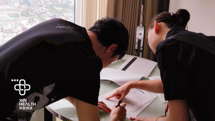 挚馨健康 XIN HEALTH 服务团队成员正在辅助用户填写体检表