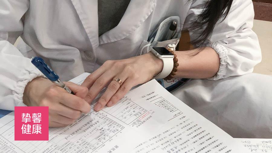 医生正在给患者看病填写诊断结果