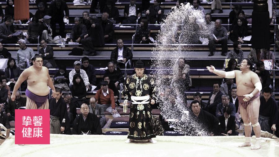 相扑力士在比赛前向空中撒盐